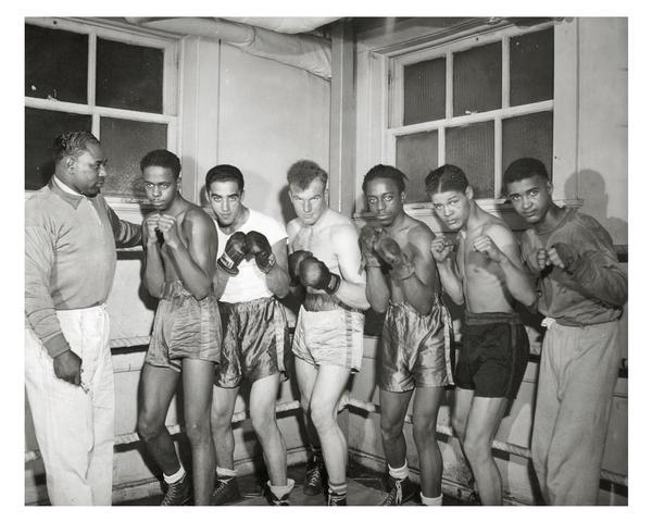 Six fighters in pugilistic poses, in the boxing ring with their coach. The Milwaukee Urban League provided community activities, like boxing, for children and adults.