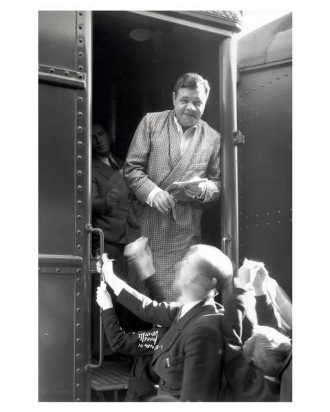 Babe Ruth, wearing a dressing gown, signing autographs from a train car during a stopover in Madison.