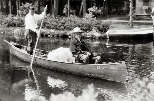 President Calvin Coolidge fishing at Cedar Island Lodge, rustic lodge of Henry C. Pierce, 35 miles from Superior, Wisconsin, on the Brule River. This lodge was later dubbed The Summer White House. The canoe is named Beaver Dick and the guide is John LaRock.