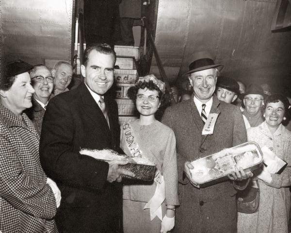 Richard M. Nixon welcomed by Barbara Bird, Honey Queen, and Wisconsin Governor Vernon W. Thomson with cheese package at the Oshkosh Airport.