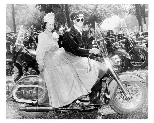 Alice in Dairyland, Marjean Czerwinski, wearing her crown and gown, rides on the back of a Harley-Davidson motorcycle.