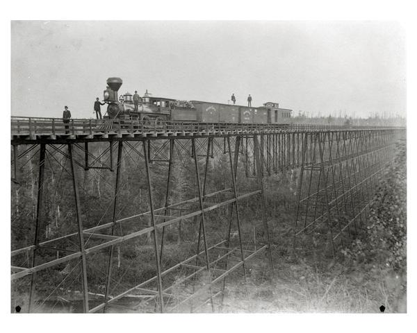 "Wisconsin Central Railroad train on White River Bridge, with crew posing on top of cars. The bridge was 1600 feet long and 110 feet above the water. In 1877 excursions were run from the South so the sight-seers might view its ""marvel of engineering."" Bridge was dismantled and sold for junk in 1909."
