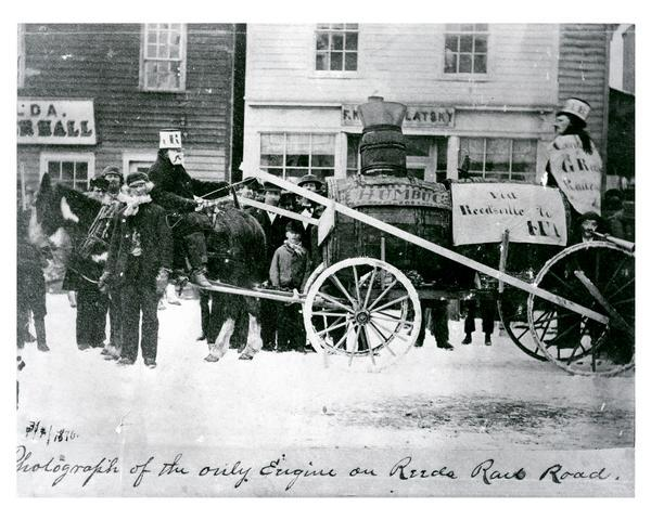 Street parade rig, apparently to agitate against delays in construction of a railroad to connect Manitowoc to the west. In the background is a store owned by F. Kostomlatsky, secretary-treasurer of the Slovanska Lipa (Bohemian Society). Kostomlatsky was a dry-goods and later wholesale liquor dealer. Next to this store is the Turner Hall, with the name Thusnelda Lodge of the Orden der Hermannsoehne, a German organization which used the building as a meeting place.