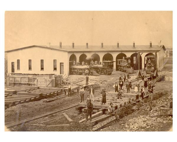 """The West Wisconsin Railway roundhouse at Eau Claire, ca. 1872. It was located about a mile north of the present Civic Center. Workmen in the foreground are building a new turntable to replace the earlier one, often call the ""gallows."" Locomotives in the stalls are Baldwin wood burners, all 4-4-0s, built in 1871. Headed out of stall 7, to the left, is engine No. 12 the ""Geo. W. Clinton""; the engine headed into stall 6, with its tender missing and the main rods down, is engine No. 14, names for ""Matt W. Carpenter""; and backed into stall 3 is engine No. 10, named the ""D.A. Baldwin."" Baldwin was one of the incorporators in 1871, of the St. Paul, Stillwater & Taylors Falls Railway. These engines all carried their same numbers even when they were taken over a few years later by the Chicago, St. Paul, Minneapolis & Omaha in 1878."""