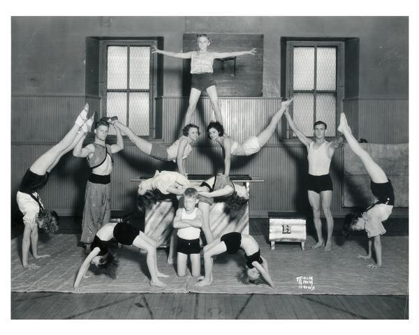 "Twelve boys and girls, coached by J.C. Haberman, in an acrobatic/gymnastic pose at the Madison Turners Hall, 21 South Butler Street. They performed seven ""acts"" at the Policemen's Protective Association benefit picnic for The Capital Times Kiddie Camp fund at the French Village in Miller's Park on South Park Street.  Madison's Turnverein was founded in 1855 by German immigrants to encourage physical and mental development."
