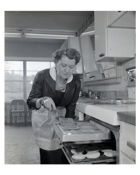 An apron-clad woman broils hamburgers in the kitchen.