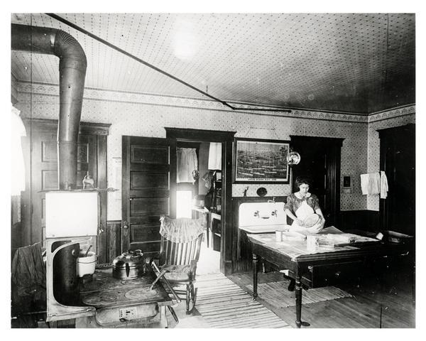 Woman baking in a large kitchen with lean-to pantry and a wood-burning stove. The sconces or reflectors on the kerosene lamps intensified the light.