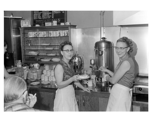 Two women serving coffee to customers at a coffee shop. Richland Center, Wisconsin.