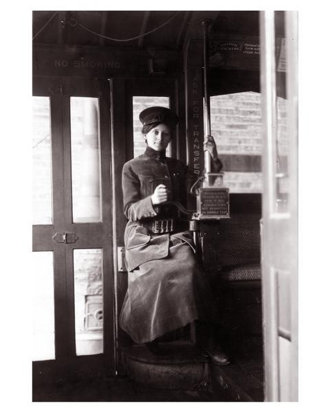 A ticket collector for the Milwaukee Electric Railway is sitting at her station.