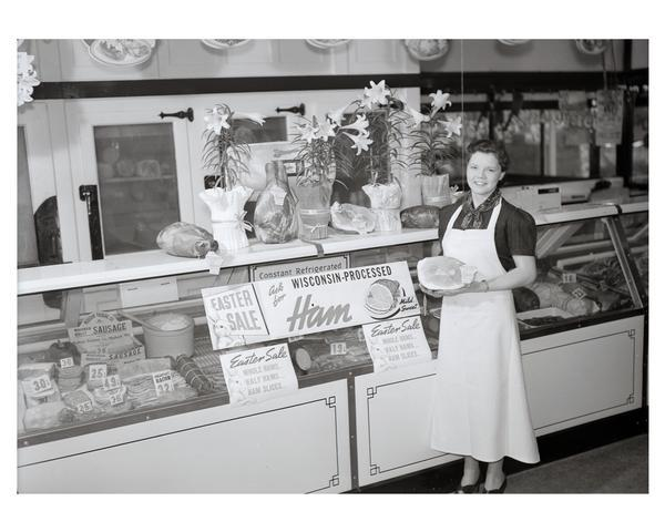 Woman worker wearing a butcher's apron, poses holding a ham, in a meat market with Easter ham display.