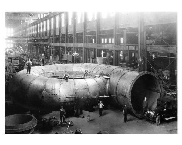 Plate Steel Spiral Casing for 70,000 horse-power Niagara Falls hydraulic turbine unit at the Allis-Chalmers Manufacturing Company erecting shop. The casting inlet diameter is 15 feet while the overall diameter is 50 feet. The plate thickness varies from 7/8 to 1 1/4 inches. Note the automobile in the lower right corner for scale.