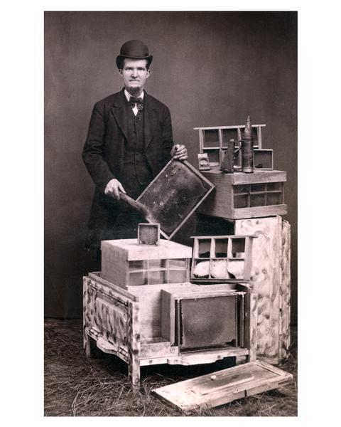 L.E. Mercer, of Lenox Iowa, posed with honey-producing equipment. Mercer is wearing a full suit, bow tie, and hat.