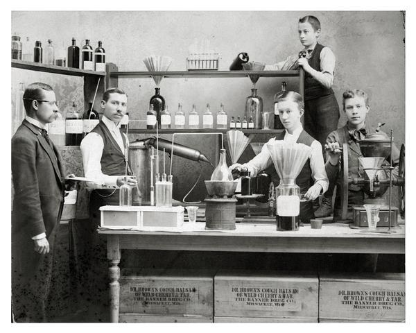 Workers pose in front of pharmaceutical equipment to demonstrate making Dr. Brown's Cough Balsam.