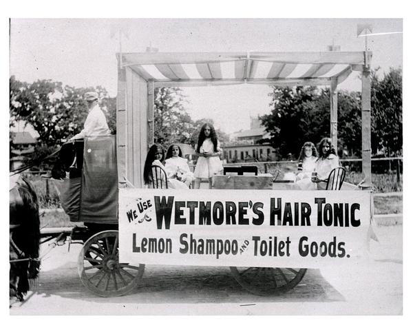 A traveling medicine wagon with saleswomen and vendor selling Westmore's Hair Tonic.