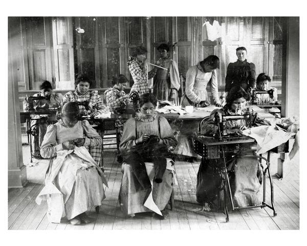 Sewing room at Lac du Flambeau U.S. Government School for Indian children. Female students posed at their sewing machines and work tables.