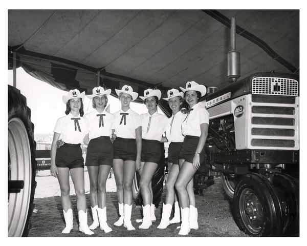 Women wearing International Harvester cowboy hats, posed in front of Farmall 460 Tractor.