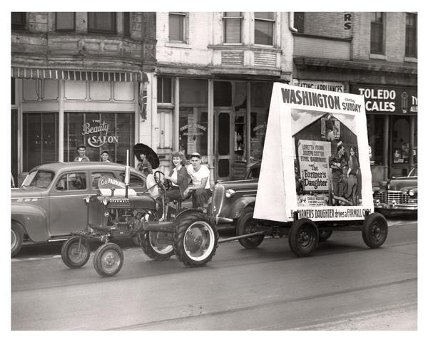 "Two people driving a Farmall Cub through an urban area. They are towing a wagon with movie advertisement, announcing ""The Farmer's Daughter,"" starring Loretta Young, Joseph Cotton, and Ethel Barrymore. The advertisement also proclaims that the Farmer's Daughter Drives a Farmall Cub."
