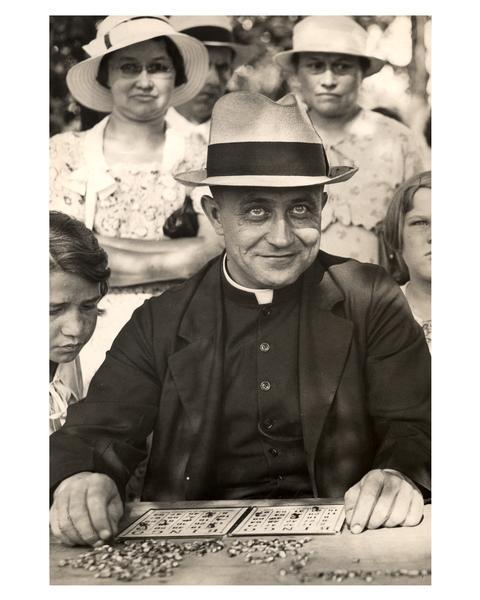 Reverend Richard Kiefer of Sacred Heart monastery in Hales Corners, Wisconsin, joins in the bingo competition at a Catholic picnic, as women and children are looking on from behind.