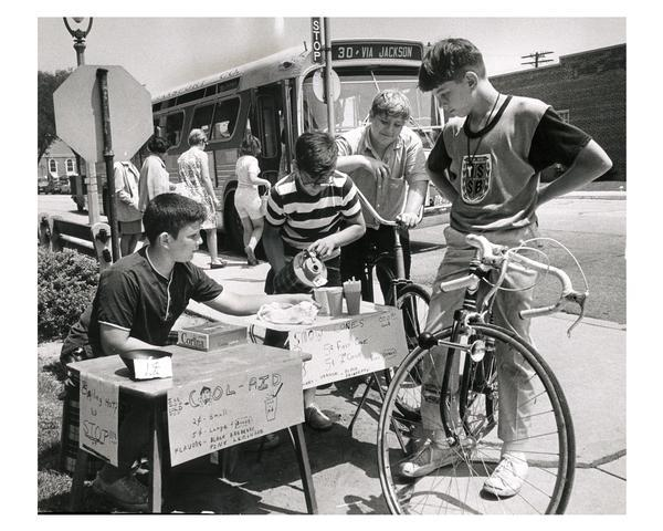Several young boys sell fruit drinks, penny candy, and snow cones to parched pedestrians. A city bus is in the background.
