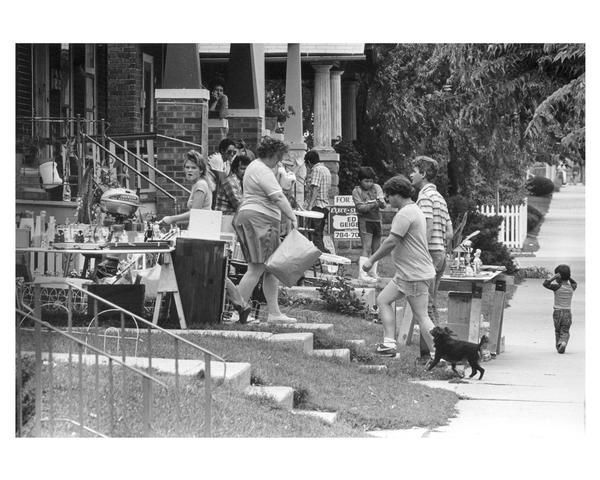 People working and shopping at a neighborhood garage sale in the Walker's Square Park area. Several neighborhood groups collaborated to sponsor the annual Southside Housing Fair and Flea Market, which featured booths on home buying, renovation, and legal matters, as well as several garage sales.