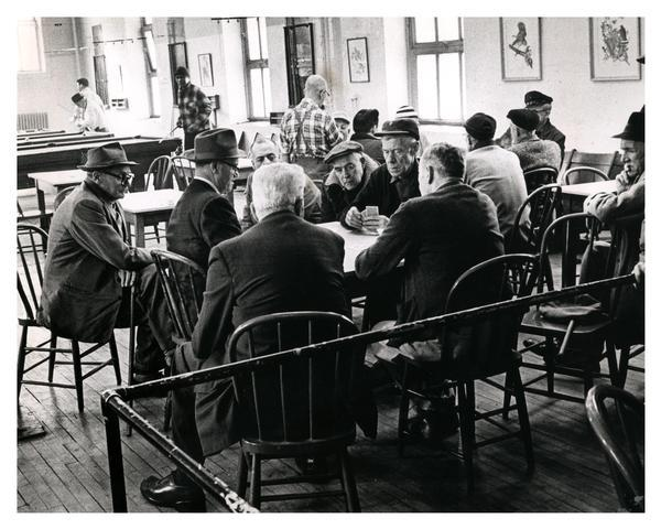 Several men engaged in a serious card game at the Milwaukee Municipal Social Center, one of several centers devoted to social and recreational programs for citizens of all ages.