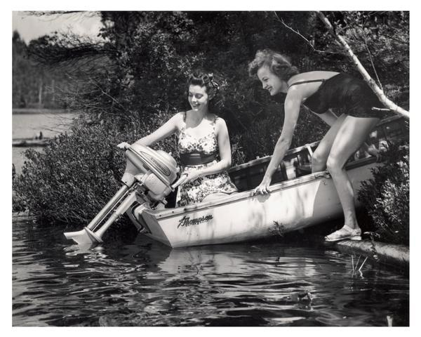 Two bathing suit-clad women demonstrating their Evinrude motorboat on a Wisconsin lake.