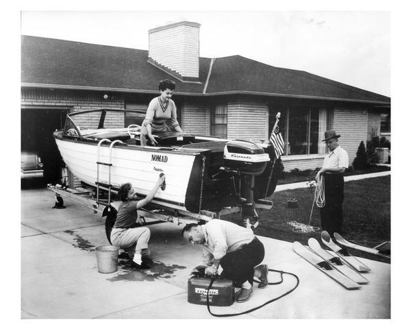 An industrious family cleans their motorboat which is parked in the driveway.