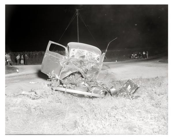View from front of Capital City Culvert Company automobile involved in an accident with a Phillips Produce Company egg truck at the intersection of County Trunk Highway M and PB, taken at 2:35 a.m. Spectators look on from across the road. Edward F. Gafke, of Basco, died in the accident.