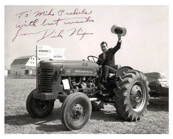 Vice President Richard M. Nixon waves his cowboy hat from the seat of an International 300 utility tractor.
