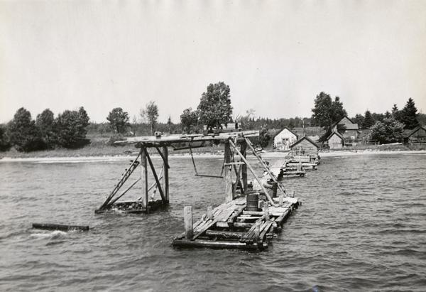 View from water of fishing dock and structure alongside; log buildings in background on shore. Possibly on shoreline of one of the Apostle Islands or on Chequamegon Bay.