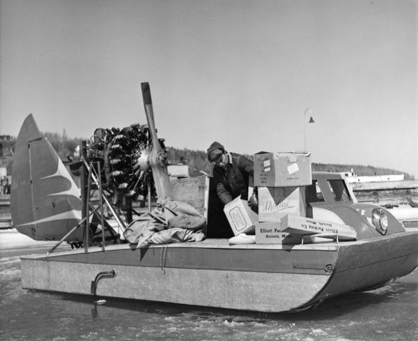 "Elmer Nelson sorting through boxes of goods being transported on the ""Dream Sled"" windsled."