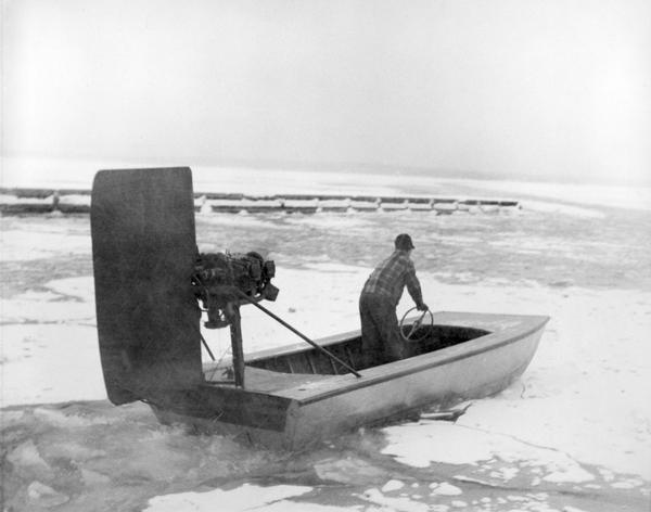Man driving windsled on frozen Lake Superior. The windsled is an open boat fitted with an engine and rudder.