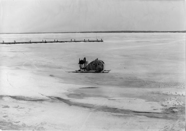 Elevated view of the enclosed wind sled shaped like the <i>Maybe</i>, sitting on the ice with La Pointe dock on the left.