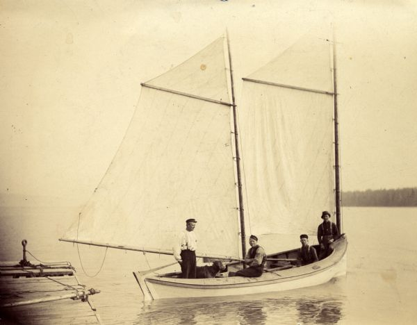 "Ole Christinson, Dick Hanson, Fred Hanson, and Herman Johnson, Sr., onboard sailboat ""Louis Moe"" along the shore of Sand Island."
