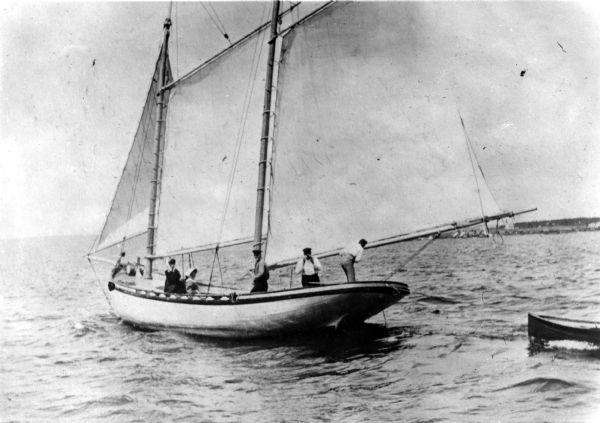 Three men and two women on board the <i>Lizzie W.</i> sailboat.  Captain D.R. Angus, who is at the tiller, owned the <i>Lizzie W.,</i> which was named after Elizabeth Woods, the wife of Mr. Frederick Woods.