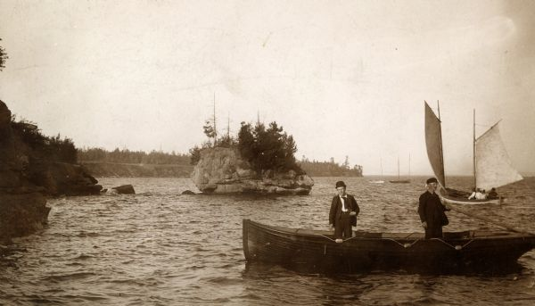 Two men standing in wooden rowboat along shore of Madeline Island.  There are sailboats in the background. Behind them is a large rock just off the shoreline, with trees growing on the side and top.