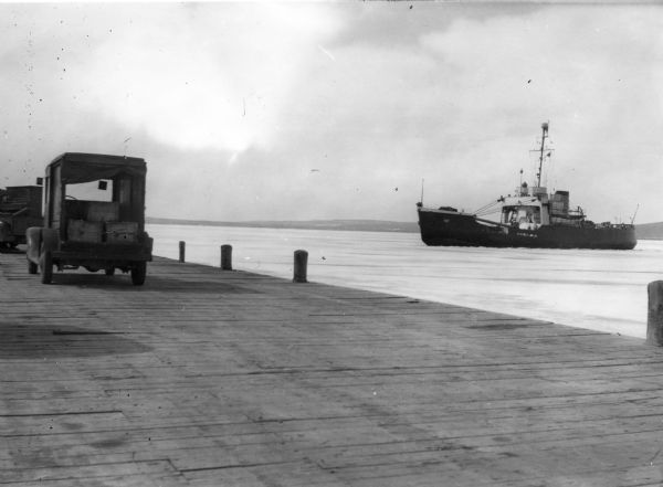 "View from dock of the U.S. Coast Guard ship ""Woodrush"" arriving at the La Pointe dock to clear ice. Two trucks are on the dock, one with a piano."