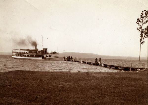 "View from shoreline of the steamboat ""Plowboy"" approaching the Mission Dock at La Pointe. The Plowboy was the first steam ferry to go to Madeline Island. The boat made regular runs between Ashland, Washburn, Bayfield, and La Pointe."
