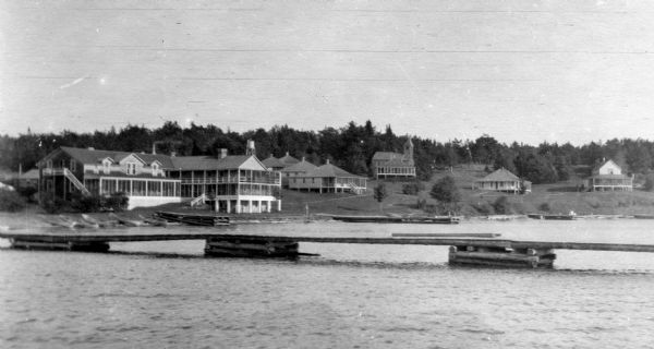 View from the water of the Mission, dock, Mission cottages, and Congregational Church on Madeline Island.