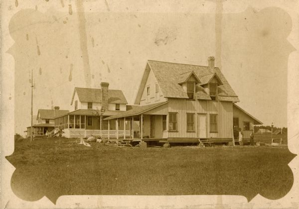 View of three of the early houses on Nebraska Row in La Pointe, Madeline Island. Haecker house is in the foreground, the Woods' house is next door.