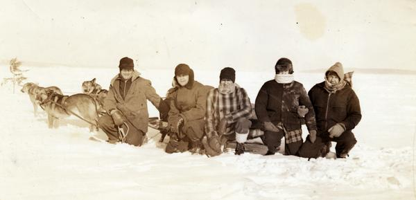Mary L. Eldridge, Dick Eldridge, Barney Johnson, and two other people kneeling in front of dog sled on Lake Superior.