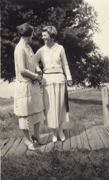 Two young women standing on a boardwalk on Madeline Island.