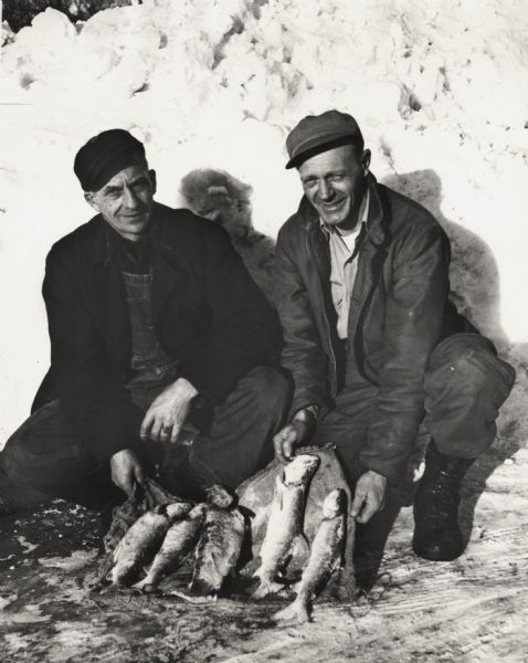 Vern Frechette (left) and Leonard Larson show their catch of trout caught during ice fishing on Chequamegon Bay.