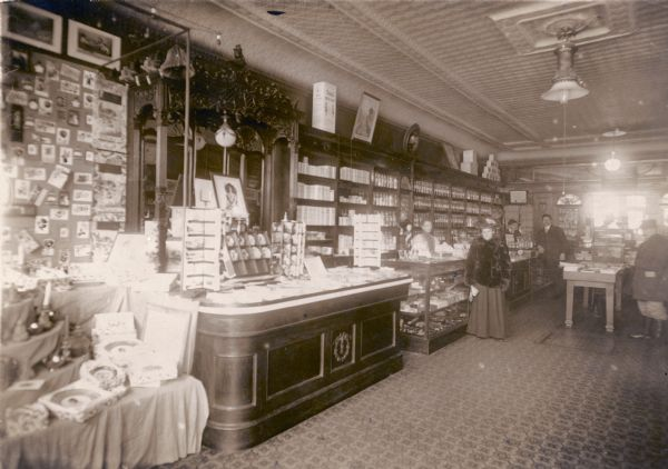 Colorful advertising displays line the counters of this turn-of-the- century drugstore, with rows of glass pharmaceutical bottles filling the shelves behind the counter.  A woman in a fur coat is served by a female clerk. One of the women is identified as Mrs. William H. Meyne.