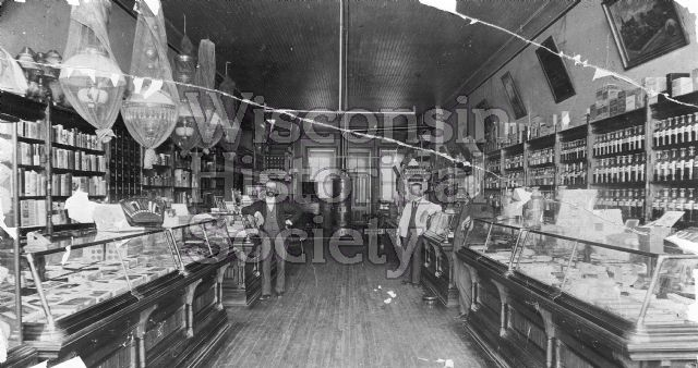 Interior view of the Kimberly & Elwers Drugstore. Pharmaceutical bottles line the shelves on the right side.