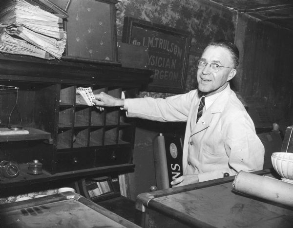 Stoughton druggist, O.N. Falk, sorts the mail with a smile.
