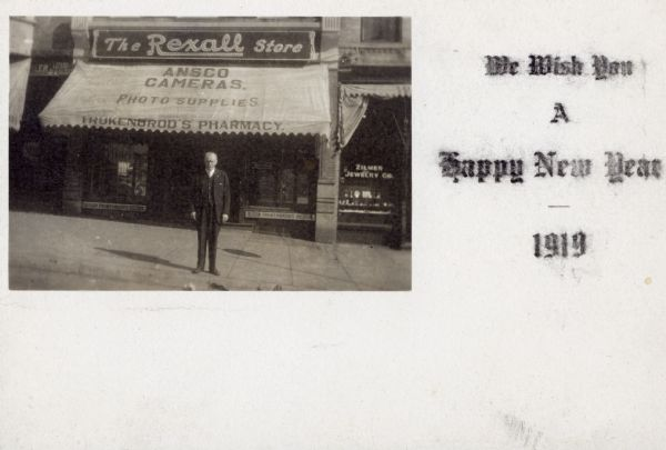 W.F. Trukenbrod poses underneath the awning of his store for this New Year's postcard.