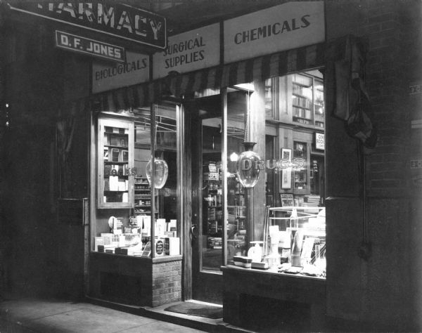 Exterior view of the D.F. Jones' Pharmacy at night. 2 large showglobes are in the display windows.