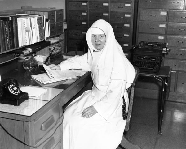 Sister Mary Clara Francis, pharmacist at St. Joseph Hospital, glances up from her paperwork.