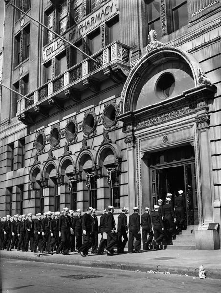 Pictured are the members of the U.S. Coast Guard Hospital Corps School heading to their pharmacy course in the Columbia University College of Pharmacy building. There were 200 people in each class, and the course required three months of intensive study before Guardsmen were prepared for active duty.